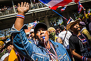 """14 JANUARY 2014 - BANGKOK, THAILAND:  Anti-government protestors blow their whistles in front of Royal Thai Police headquarters. The whistle has emerged as the protestors' main weapon against the government. Hundreds of protestors picketed police headquarters because they accuse the police of siding with the government during the protests. Tens of thousands of Thai anti-government protestors continued to block the streets of Bangkok Tuesday to shut down the Thai capitol. The protest, """"Shutdown Bangkok,"""" is expected to last at least a week. Shutdown Bangkok is organized by People's Democratic Reform Committee (PRDC). It's a continuation of protests that started in early November. There have been shootings almost every night at different protests sites around Bangkok, but so far Shutdown Bangkok has been peaceful. The malls in Bangkok are still open but many other businesses are closed and mass transit is swamped with both protestors and people who had to use mass transit because the roads were blocked.    PHOTO BY JACK KURTZ"""