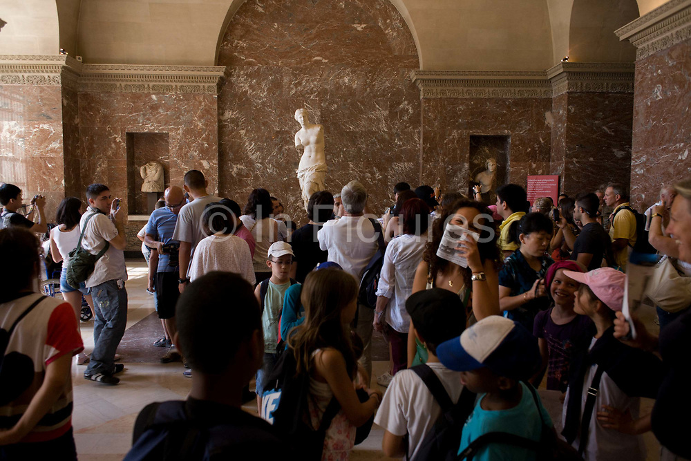 Tourists admire Aphrodite, otherwise known as the Venus de Milo in the Louvre art museum. The ancient Greek statue is one of the most famous works of ancient Greek sculpture, created sometime between 130 and 100 BC. The Aphrodite (Greek goddess of love and beauty  and Venus to the Romans) is a marble sculpture, slightly larger than life size at 203 cm high. The arms and original plinth were lost following the discovery. From an inscription that was on its plinth, it is thought to be the work of Alexandros of Antioch; earlier, it was mistakenly attributed to the master sculptor Praxiteles. The Musée du Louvre is one of the world's largest museums and the most visited art museum in the world.