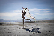 Photo of a nude woman leaping on the Great Salt Lake, Utah waving a long scarf