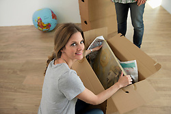 Woman unpacking painting inside box at home