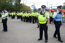 London, UK. 3 September, 2019. Metropolitan Police officers arrive to disperse hundreds of Quakers, joined by fellow peace activists and representatives of other faith groups, holding a religious service in the access road outside ExCel London as part of the day's No Faith In War activities in protest against DSEI, the world's largest arms fair.