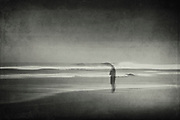 Stormy beach - man standing in the surf - abstract photography