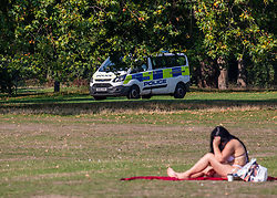 "© Licensed to London News Pictures. 15/09/2020. London, UK. A sunbather enjoys the warm sunshine this morning as Police patrol Hyde Park enforcing the ""Rule of Six"" as the mini-heatwave continues in the South East of England with highs of 29c. Prime Minister Boris Johnson announced last week that gatherings of more than six people will be banned from Monday (yesterday) in the hope of reducing the coronavirus R number. The Rule of Six has already become unpopular with MPs and large families for being too strict. Photo credit: Alex Lentati/LNP"