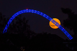 © Licensed to London News Pictures. 05/07/2020. WEMBLEY, UK.  July's full moon, known as a Buck Moon, rises behind Wembley Stadium in north west London.  In the Farmers' Almanac, the Buck Moon is so named named after the new antlers that emerge from a buck's forehead around this time of the year.  The arch of the stadium's are lit up in blue to commemorate the 72nd birthday of the National Health Service (NHS) and to thank all NHS workers for their efforts during the ongoing coronavirus pandemic.  Photo credit: Stephen Chung/LNP