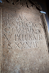 """© Licensed to London News Pictures 25/01/2016, Cirencester, UK. A unique Roman tombstone, found in February 2015, goes on display for the first time at Corinium Museum in Cirencester. The tombstone was found near skeletal remains thought to belong to the person named on its inscription, making the discovery unique. After being found during excavation works on a former site of a garage, archaeologists said they believed it marked the grave of a 27-year-old woman called Bodica. Other theories point to it possibly belonging to a couple - as skeletal remains of women were found nearby.<br /> The inscription reads """"To the shades of the dead, Bodicacia spouse lived 27 years"""". Photo Credit : Stephen Shepherd/LNP"""
