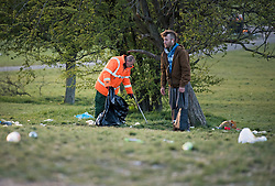© Licensed to London News Pictures. 18/04/2021. London, UK. A council worker collects litter strewn across the top of Primrose Hill in North London, despite the park being closed from 10pm last night. A curfew has been put in to place at the park over the weekend  to prevent large gatherings in the evening. Photo credit: Ben Cawthra/LNP