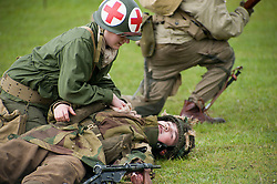 Renactor portraying a US field Medic gives aid to a reenactor from the British 6th Airborne during a battle reenactment at Fort Paull Monday.7  May 2012.Image © Paul David Drabble