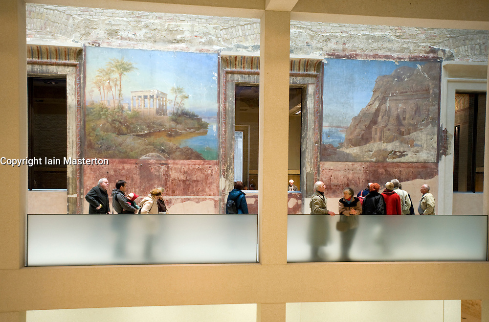 Visitors looking at old murals on wall in Egyptian courtyard gallery of newly renovated and reopened Neues Museum in Berlin 2009
