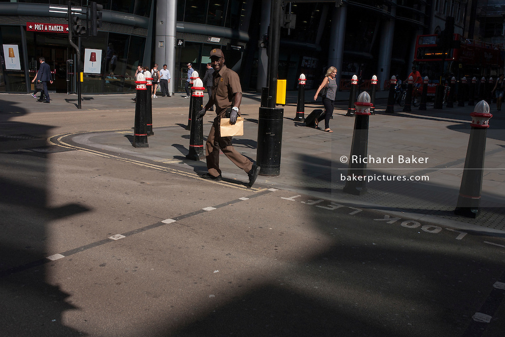 A UPS courier grins during a summer heatwave on Cannon Street in the City of London, UK.