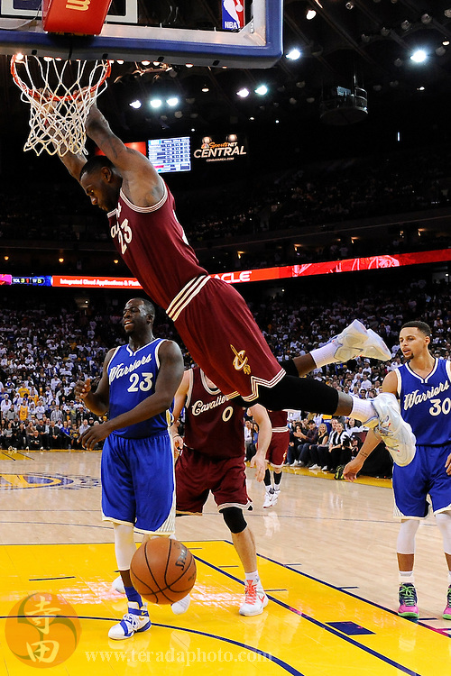 December 25, 2015; Oakland, CA, USA; Cleveland Cavaliers forward LeBron James (23, top) dunks the basketball against Golden State Warriors forward Draymond Green (23, bottom) during the fourth quarter in a NBA basketball game on Christmas at Oracle Arena. The Warriors defeated the Cavaliers 89-83.