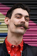 Young man in late-twenties street portrait with moustache.