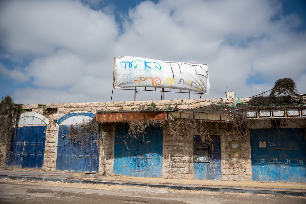 2 March 2020, Hebron: An election sign sits above closed shops on the Al-Shuhada Street in the H2 area of Hebron. The area is under Israeli military control, and following the 1994 massacre at the Tomb of the Patriarchs (known to the Muslims as Al-Ibrahimi Mosque and to the Jews as Cave of Machpelah) all the Palestinian shops on Shuhada street have been closed, turning the street into a virtual ghost town.