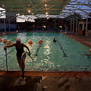 Despite having to rely on a cane and a walker to help her get around due to Multiple Sclerosis, Margo Bouer exits the pool during synchronized swimming at the Laguna Woods Village clubhouse pool.
