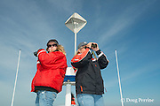 senior scientist Dr. Moira Brown and research intern Johanna Anderson scout the Bay of Fundy for North Atlantic right whales on the New England Aquarium research vessel Nereid in Grand Manan Basin, Bay of Fundy ( North Atlantic Ocean ), New Brunswick, Canada