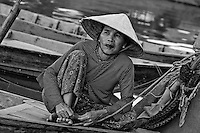 Older woman wearing a traditional conical hat sitting on a boat in Vietnam.