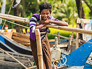 06 NOVEMBER 2014 - SITTWE, RAKHINE, MYANMAR: A Rohingya Muslim fishing crewman on a boat at the pier in a Rohingya IDP camp near Sittwe. After sectarian violence devastated Rohingya communities and left hundreds of Rohingya dead in 2012, the government of Myanmar forced more than 140,000 Rohingya Muslims who used to live in and around Sittwe, Myanmar, into squalid Internal Displaced Persons camps. The government says the Rohingya are not Burmese citizens, that they are illegal immigrants from Bangladesh. The Bangladesh government says the Rohingya are Burmese and the Rohingya insist that they have lived in Burma for generations. The camps are about 20 minutes from Sittwe but the Rohingya who live in the camps are not allowed to leave without government permission. They are not allowed to work outside the camps, they are not allowed to go to Sittwe to use the hospital, go to school or do business. The camps have no electricity. Water is delivered through community wells. There are small schools funded by NOGs in the camps and a few private clinics but medical care is costly and not reliable.   PHOTO BY JACK KURTZ