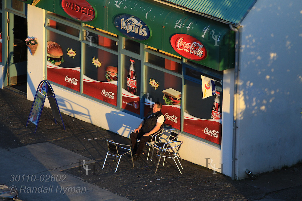 Man sits in front of small shop late on a summer evening in western Reykjavik, Iceland.