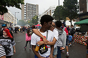 Near to Trellick Tower on Sunday 28th August 2016 at the 50th Notting Hill Carnival in West London. A celebration of West Indian / Caribbean culture and Europes largest street party, festival and parade. Revellers come in their hundreds of thousands to have fun, dance, drink and let go in the brilliant atmosphere. It is led by members of the West Indian / Caribbean community, particularly the Trinidadian and Tobagonian British population, many of whom have lived in the area since the 1950s. The carnival has attracted up to 2 million people in the past and centres around a parade of floats, dancers and sound systems.