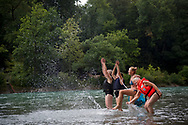 Bern, Switzerland - August 14, 2018: Four sisters enter the Aare River at the Eichholz Camping beach to float downstream.