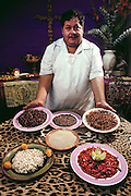 Fortino Rojas, the chef at Don Chon, a Mexico City restaurant specializing in pre- Hispanic dishes, including insects. Bottom row of plates, L to R: escamoles (giant ant larvae), and river crawfish; center: ahuauatles (fly larvae from Lake Texcoco); top row, L to R: chapulines (fried grasshoppers), jumiles (stink bugs), and red maguay worms..Image from the book project Man Eating Bugs: The Art and Science of Eating Insects.