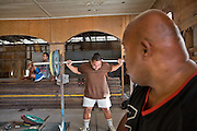 Gerard advising Roland Raboe..Gerard Jones (R, age 47, super class, 143 kg), is the national trainer..Nauru's Weightlifting Gym in Aiwo District (Aiwo's Boys Gym). Girls and boys train here every day starting at 5pm. Nauru's weightlifting champions (including the President of Nauru) have won several gold medals at the Commonwealth Games. Weightlifting is the pride of the nation..Although Nauru is the world's fattest country, with 94% of its population being overweight, teenagers are very fit and sportive. Amongst the favorite sports are weightlifting, Aussie Rule football (a kind of Rugby) and boxing. ..Nauru, officially the Republic of Nauru is an island nation in Micronesia in the South Pacific.  Nauru was declared independent in 1968 and it is the world's smallest independent republic, covering just 21square kilometers..Nauru is a phosphate rock island and its economy depends almost entirely on the phosphate deposits that originate from the droppings of sea birds. Following its exploitation it briefly boasted the highest per-capita income enjoyed by any sovereign state in the world during the late 1960s and early 1970s..In the 1990s, when the phosphate reserves were partly exhausted the government resorted to unusual measures. Nauru briefly became a tax haven and illegal money laundering centre. From 2001 to 2008, it accepted aid from the Australian government in exchange for housing a Nauru detention centre, with refugees from various countries including Afghanistan and Iraq..Most necessities are imported on the island..Nauru has parliamentary system of government. It had 17 changes of administration between 1989 and 2003. In December 2007, former weight lifting medallist Marcus Stephen became the President.