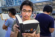 "29 MAY 2014 - BANGKOK, THAILAND: A man reads ""1984"" during a protests against the Thai coup Thursday. About eight people gathered at the Chong Nonsi intersection in Bangkok to silently read George Orwell's ""1984"" and other books about civil disobedience. The protests are based on the ""Standing Man"" protests that started in Turkey last summer. Authorities made no effort to stop the protest or interfere with the people who were reading.   PHOTO BY JACK KURTZ"