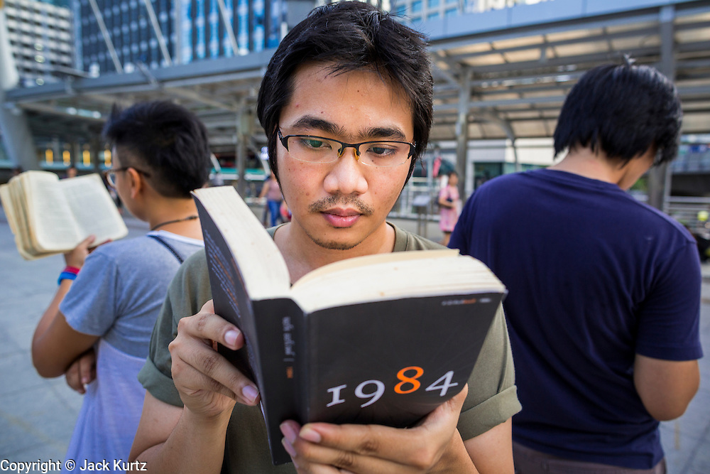 """29 MAY 2014 - BANGKOK, THAILAND: A man reads """"1984"""" during a protests against the Thai coup Thursday. About eight people gathered at the Chong Nonsi intersection in Bangkok to silently read George Orwell's """"1984"""" and other books about civil disobedience. The protests are based on the """"Standing Man"""" protests that started in Turkey last summer. Authorities made no effort to stop the protest or interfere with the people who were reading.   PHOTO BY JACK KURTZ"""