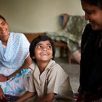 """Vasanti (left) with her youngest daughter Vrinda and her teacher at the school she attends in Sangli. ..Like many of the women who work for and with UNDP partners the Save Foundation, Vasanti Shinde, age 26, only found out that she was HIV positive after her husband became seriously ill with an AIDS-related illness five years ago. Vasanti's husband subsequently died. Vasanti now lives with her two younger daughters Shrudha, age 10, and Vrinda, 8, in the one-room home of her brother in Sangli city. Vasanti's elder daughter, eleven year old Shubhada is being brought up by her paternal grandmother and sees her mother during holidays. Vasanti knows that Shubhada is HIV negative and Shruda is positive but anxiety over the result means that she refuses to have Vrinda tested for HIV. For a monthly income of Rs.3500, Vasanti works as a field officer and counselor for the Save Foundation. She works in the positive-people's pharmacy for no pay. Her work with the Save Foundation entitles her access to a credit union which provides low interest loans covering medical expenses. Though first-line drugs and homeopathic medicine keep Vasanti healthy, she is prone to infection and recently suffered a bout of influenza. Vasanti is completely open about her HIV status and most of her neighbours know that she is HIV positive. Vasanti says that """"I used to feel like I was going to die. Now, because of the Save Foundation, I feel like I'm going to live."""" ..Photo: Tom Pietrasik.Sangli, Maharashtra. India.August 27th 2008..THIS PHOTOGRAPH IS THE COPYRIGHT OF TOM PIETRASIK. THE PHOTOGRAPH MAY NOT BE REPRODUCED IN ANY FORM OTHER THAN THAT FOR WHICH PERMISSION WAS GRANTED. THE PHOTOGRAPH MAY NOT BE STORED OR MANIPULATED WITHOUT PRIOR PERMISSION FROM TOM PIETRASIK...Tom Pietrasik.PHOTOGRAPHER.NEW DELHI.India tel: +91 9810614419.UK tel: +44 7710507916.Email: tom@tompietrasik.com.Website: tompietrasik.com"""