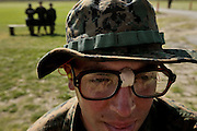 Recruit Tampanello, NY, has a makeshift stabilizer on his glasses to keep them from moving when he shoots on the range.  In the background 3 fellow recruits guard the ammunition.   Marine Corps Recruit Depot at Parris Island in South Carolina is where all male recruits living east of the Mississippi River and all female recruits from all over the US receive their arduous twelve week training in their quest to become marines. Even though there are two current active wars and a weak economy, recruitment has not been effected.  Actually, recruiting numbers have increased, with more young men and women looking toward the military for answers.