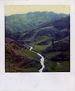 Old Polaroid of terraced rice fields and a winding river inside a valley in the mountainous landscape of Northern Vietnam, Southeast Asia