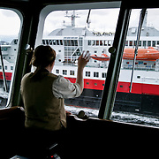 Three weeks aboard the Kong Harald. Hurtigruten, the Coastal Express. The bridge of the Kong Harald. A waitress is looking at the Polarys through the windows of the bridge.