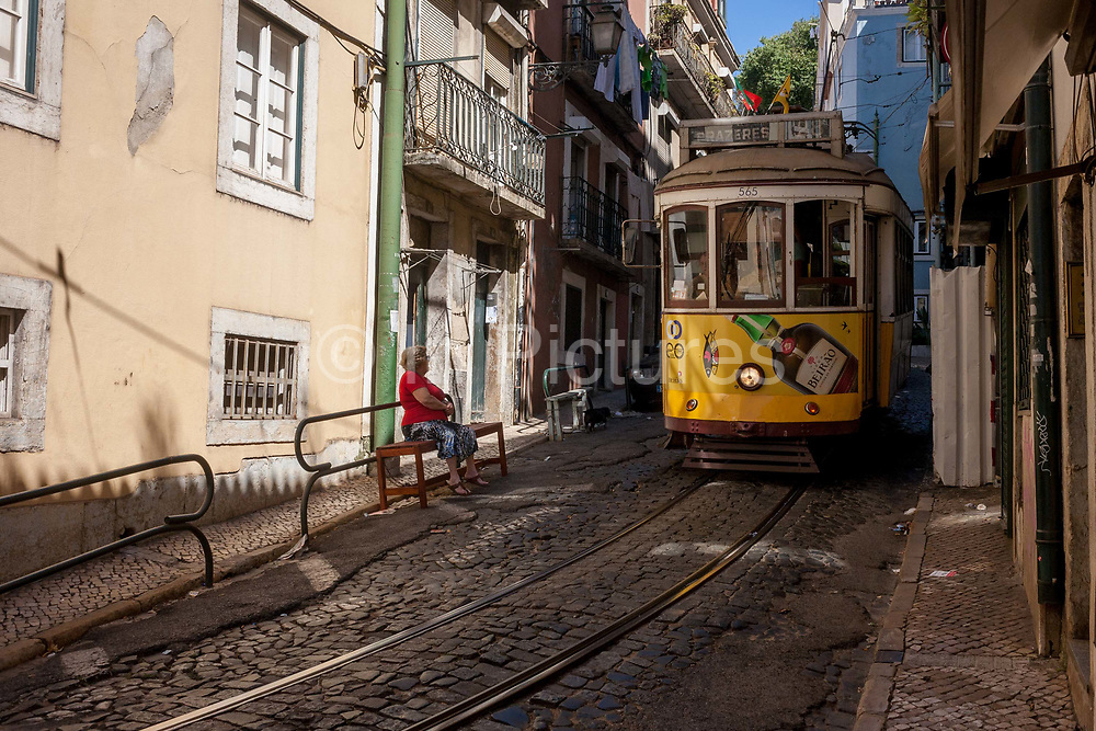 As a local lady looks on from her street bench, as a number 28 tram edges slowly through a steep and narrow street, on 11th July 2016, in Lisbon Portugal. The 28 is one of the trams not only used by the people of the capital but also of an increasing number of tourists who ride the entire route from Prazeres cemetery in the west of the city, to Rossio in the centre, after a loop through some of the most amazing streets and landmarks. So crowded is the 28, that older locals often cant sit down, having to stand over younger, inconsiderate tourist families who want a window seat for the entire journey - and back. Notices at termini remind visitors that this is a public service and to consider locals.