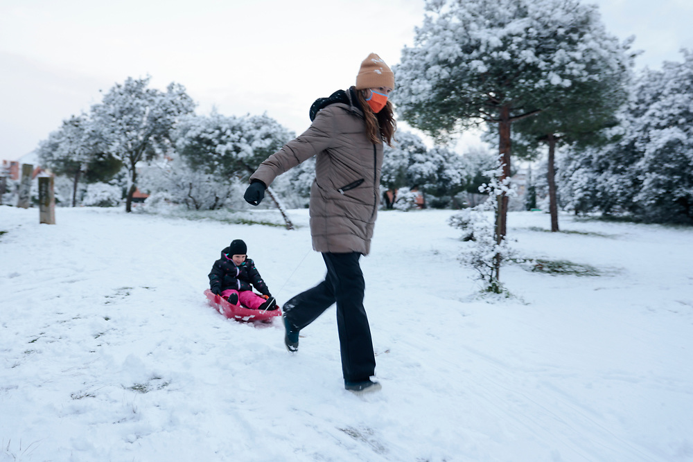 MADRID, SPAIN - JANUARY 7: A woman wearing a face mask, pulls her son on a sled on the snow at a public park covered in snow as storm Filomena hits the area on January 7, 2021, in Majadahonda, Madrid, Spain.