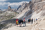 """Walk towards Rifugio Locatelli (Dreizinnenhütte) in the Sexten Dolomites Nature Reserve (Parco Naturale Dolomiti di Sesto, or Naturpark Sextner Dolomiten), Italy, Europe. Hike for spectacular views around Tre Cime di Lavaredo (Italian for """"Three Peaks of Lavaredo,"""" also called Drei Zinnen or """"Three Merlons"""" in German). Until 1919 the peaks formed part of the border between Italy and Austria. Now they lie on the border between the Italian provinces of South Tyrol and Belluno and still are a part of the linguistic boundary between German-speaking and Italian-speaking majorities. The Dolomites were declared a natural World Heritage Site (2009) by UNESCO."""