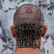 "Alexandre Helios Motta, 37 one of the most fanatical  ardent of Corinthians FC fans. His body is covered in his team's tattoos. For him Corinthians FC is bigger more important then anything else in life. His association with the club runs from birth and he can see the team's HQ from his home in Sao Paulo. He never misses any of their games including those that take place abroad even going as far as Japan when Corinthians played against Chelsea in 2013 World football championship or the Libertadores cup across South America. He forms part of one of the hard corp groups of fan clubs known as ""Gavioes da Fiel"", known as ""torcidas organizadas"", Sao Paulo, 2013."
