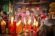 """10 FEBRUARY 2013 - BANGKOK, THAILAND:   People pray at a small Chinese shrine on Chareon Krung Road in the Chinatown section of Bangkok on Chinese New Year. Bangkok has a large Chinese emigrant population, most of whom settled in Thailand in the 18th and 19th centuries. Chinese, or Lunar, New Year is celebrated with fireworks and parades in Chinese communities throughout Thailand. The coming year will be the """"Year of the Snake"""" in the Chinese zodiac.  PHOTO BY JACK KURTZ"""