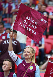 An Aston Villa fan in the stands waves a flag during the Sky Bet Championship Final at Wembley Stadium, London.