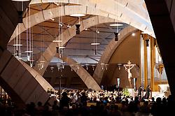 """È stata inaugurata il 1° luglio 2004, la nuova Chiesa di San Pio da Pietrelcina progettata dall'architetto Renzo Piano. Esattamente 45 anni prima, nel 1959,  veniva inaugurata la chiesa """"grande"""" di Santa Maria delle Grazie. .Sorta a fianco del santuario e convento in cui visse il frate, ha la forma di una conchiglia e la sua pianta ricorda quella della spriale archimedea. Enormi archi parto dal perimetro esterno e terminano nel fulcro della """"conchiglia"""" dove è posto l'altare. Possenti staffe d'acciaio, ancorate agli archi, sorreggono la volta che ricoperta di rame preossidato espone alla vista un intenso un colore verde-rame.   .Con i suoi 6000 mq, è la seconda chiesa più grande in Italia per dimensioni, dopo il Duomo di Milano. Può ospitare oltre 7000 persone e per la sua realizzazione sono state impiegati 30.000 metri cubi di calcestruzzo, 1.320 blocchi in pietra di Apricena, 70.000 metri cubi di scavo in roccia, 60.000 chili di acciaio, 500 mq di vetro, 19.500 mq di rame preossidato. Ogni anno è meta di oltre sei milioni di pellegrini..Nella foto la parte interna della chiesa con i suoi archi che si incrociano in un gioco di linee curve mentrw è in corso una celebrazione eucaristica."""