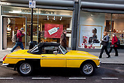 Classic MGB Midget car parked on a London street. Bright yellow this little sports car is an icon in motor vehicle history.