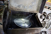 Vinyl test disk being washing in silver nitrate solution in a factory process. The Vinyl Factory is the old EMI vinyl works in Uxbridge, Middlesex, producing limited edition vinyls of new releases, plus re-presses of classics. They also act as a distributor of vinyl releases.