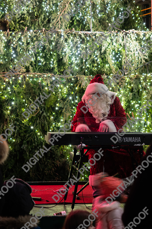 Zurich, Switzerland - December 22, 2018 A person disguised as Santa Clause play Christmas music with an electronic piano in front of christmas three.