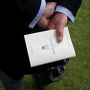 A race goer holds a racing book before the start of the races at Royal Ascot Race Course. Royal Ascot is one of the most famous race meetings in the world, frequented by Royalty and punters from the high end of society to the normal everyday working class. Royal Ascot 2009, Ascot, UK, on Tuesday, June 16, 2009. Photo Tim Clayton