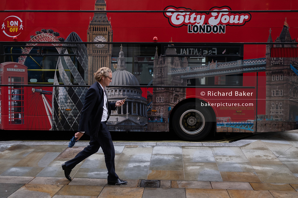 A man wearing a suit and looking at his phone, strides past a London city tour bus parked in Coventry Street in the West End, on 24th September, in London, England.