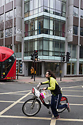The day after Facebook's Mark Zuckerberg faced Senate Committee questions in Washington, a cyclist pushes his bike over New Oxford Street outside the offices of Cambridge Analytica, the UK tech company accused of harvesting the personal details of Facebook users (including Zuckerberg himself) in its data privacy scandal, on 11th April, 2018, in London, England.