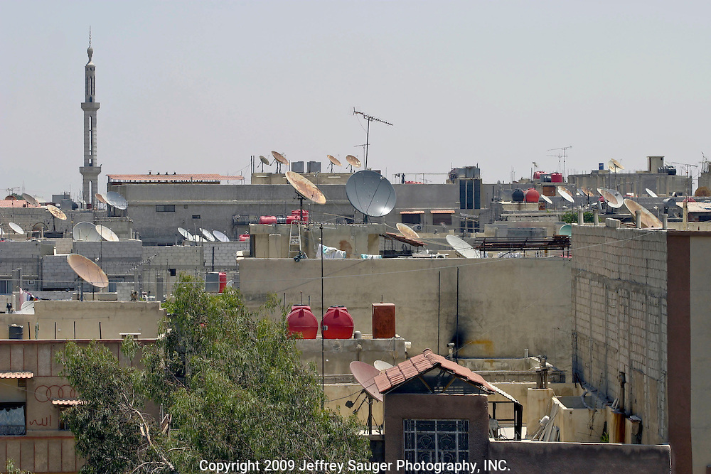 Satellite dishes and drinking water tanks line the rooftops of apartments in the Iraqi area of Damascus, Syria, July 14, 2003. Hundreds of thousands of Iraqi Shiite settled in Syria after the Gulf War and their uprising against Saddam Hussein in 1991. The spire is one of the many Shiite mosques in the area.