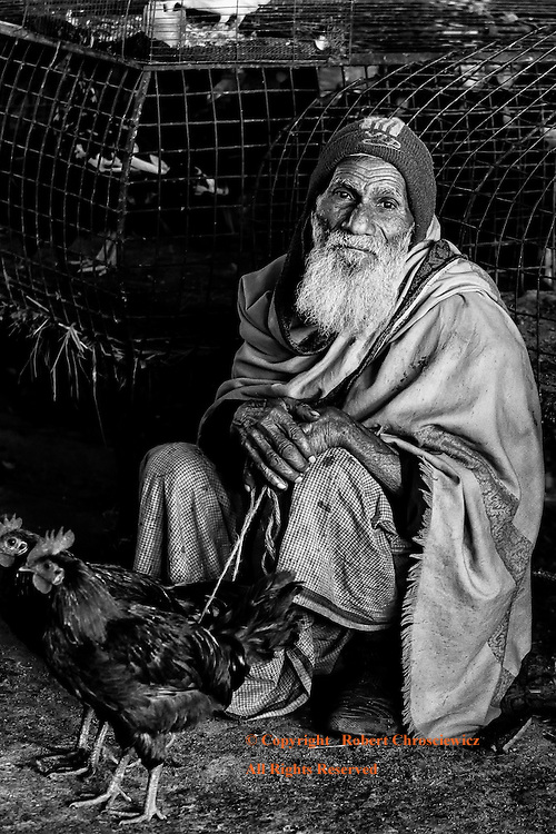 Elderly and Alone (B&W):  An elderly man sits, in quiet reflection in a vacated part of the local market, with two chickens; the sum total of his life's' toil, Srimangal Bangladesh.
