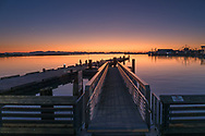 The sunset over the mountains of Vancouver Island with the Imperial Landing Docks and Steveston Harbour in the foreground.  Photographed from the Steveston Harbour Pier (attached to the docks) in Richmond, British Columbia, Canada.