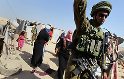 August 14, 2017 - Hebron, West Bank, Palestinian Territory - Israeli troops stand past the belongings of Palestinians as they arrive to demolish houses in the bedouin village of Khashm al-Daraj in the southern area of Yatta, south of the West Bank city of Hebron.  (Credit Image: © Wisam Hashlamoun/APA Images via ZUMA Wire)