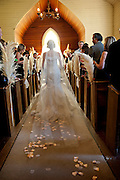 A bride walks down the aisle at, The Emmanuel Church, located in the Marshall Gold Discovery State Historic Park on her wedding day in Coloma, California.