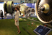 A young woman stands in front of a turbofan of engine manufacturer CFM during the Paris Air Show exhibition at Le Bourget airfield